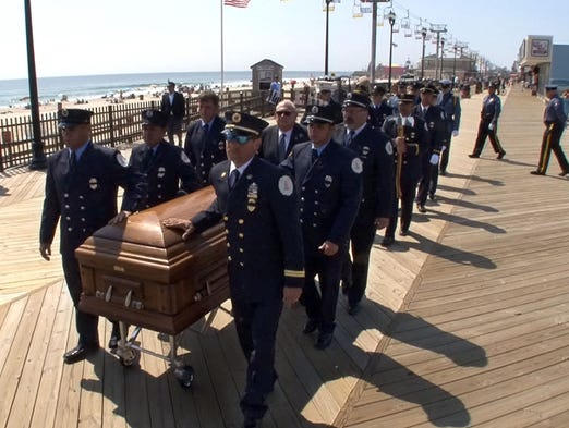 Firefighters escort former Seaside Heights Mayor Ken Hershey's casket down the boardwalk Thursday, August 7, 2014, where his funeral service was held.