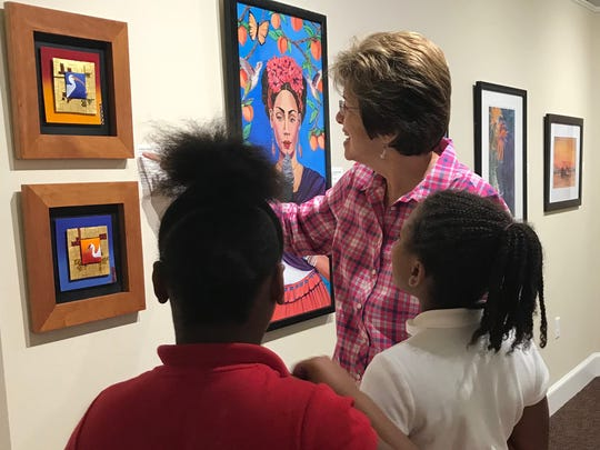 Volunteer Carole Fletcher and students discuss enamel paintings by Kathleen Wilcox and a colorful acrylic painting by Janice McCaskill during their tour of the 29th Art in Gadsden exhibition.