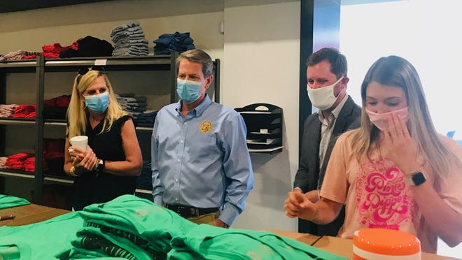 Gov. Brian Kemp and his wife, Marty check out the COVID-19 relief t-shirt operation by downtown merchandizing firm Showpony with co-owner Sean Mooney.
