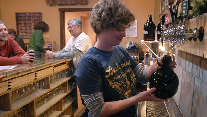 Cathy Jones of Pateros Creek Brewery fills a growler in this file photo.