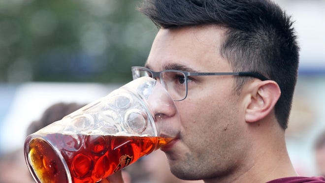 Alex Schulze, of West Chester, enjoys a beer at Oktoberfest Zinzinnati last year.