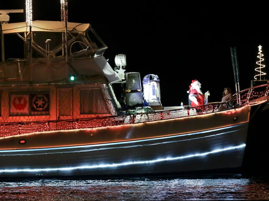 Santa waves to spectators while looking over the bow