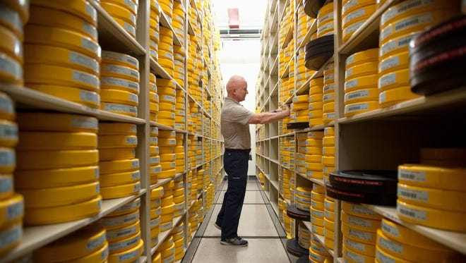 NFL Films employee Hugh Colan inspects film reels in the film vault at NFL Films headquarters in Mount Laurel.