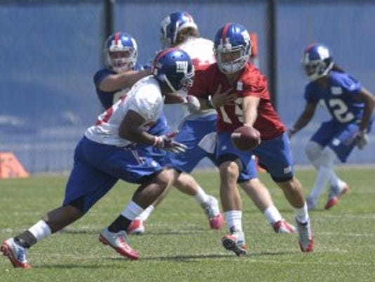 Giants quarterback Gary Nova (15) hands off to running back Anthony Cade during rookie mini-camp practice.(Photo: AP)