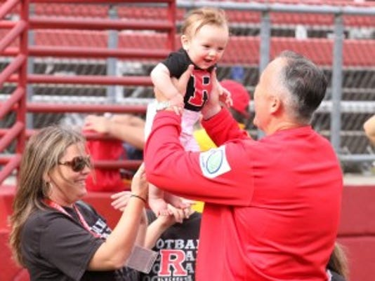 Rutgers coach Kyle Flood lifts his youngest child, Joseph, after a win against Connecticut in October 2012. (Photo: File photo)