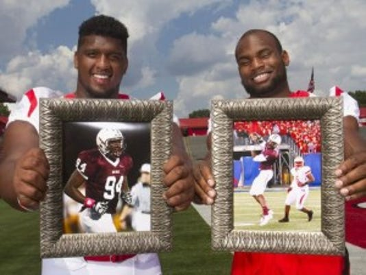 Teammates for eight straight seasons, Rutgers stars Darius Hamilton, left, and Leonte Carroo hold photos from their days a teammates at Don Bosco Preparatory High School.(Photo: Jason Towlen/Staff Photographer)