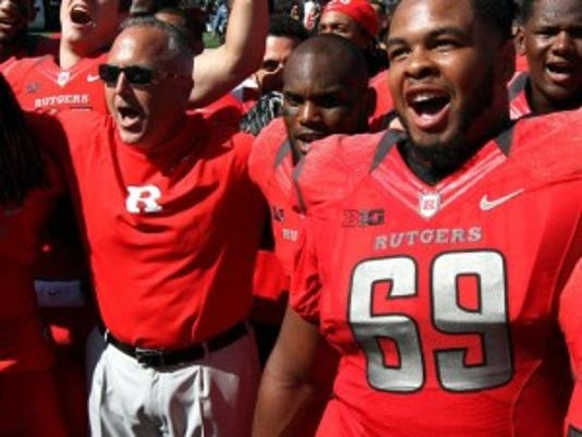 Rutgers coach Kyle Flood, flanked by his players, sings the school's alma mater after Saturday's season-opening win.(Photo: Kathy Johnson/Staff photographer)