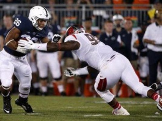 Rutgers defensive lineman Djwany Mera reaches for Penn State halfback Saquon Barkley during Saturday's game.(Photo: AP)