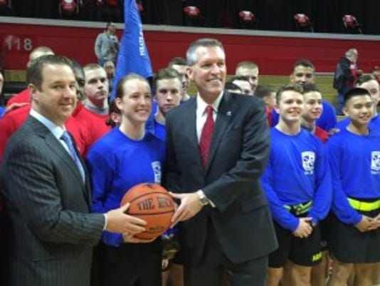 Seton Hall AD Pat Lyons (left) and Rutgers AD Pat Hobbs (right) accept the game ball from ROTC members who ran it 21 miles from Walsh Gym to the RAC.
