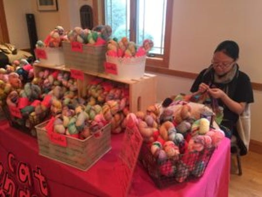 An independent dyer knits at her vendor booth at the North Jersey Fiber Arts Festival, Oct. 1, 2016.