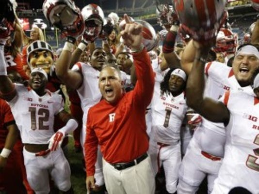 Rutgers coach Kyle Flood and his players celebrate Thursday's victory against Washington State. (AP)