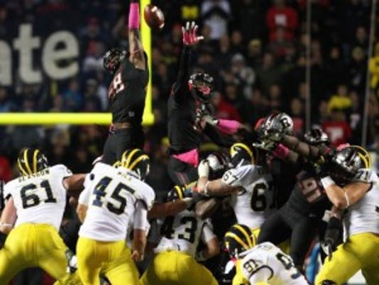 Kemoko Turay (top, left) skies to block a 56-yard field goal in the final three minutes of Rutgers' win against Michigan. (Mark Sullivan/Staff photographer)