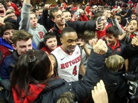 Rutgers senior guard Myles Mack is engulfed by fans after leading the stunning upset of No. 4 Wisconsin. (Jason Towlen/Staff photographer)