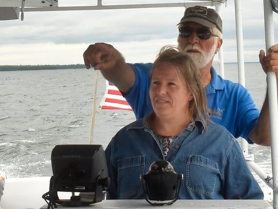 Capt. Lynn Brunsen, back, allows passenger Nicole Wolf-Murphy