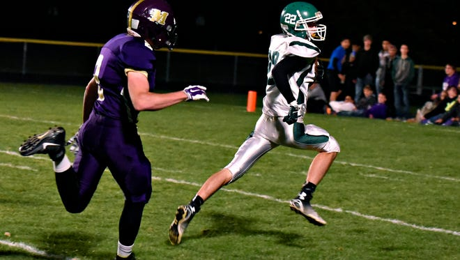 Holdingford's Blake Patrick look over his shoulder at Melrose's Hunter Radamacher as he goes into the end zone to score in the first half Wednesday, Oct. 14 in Melrose.