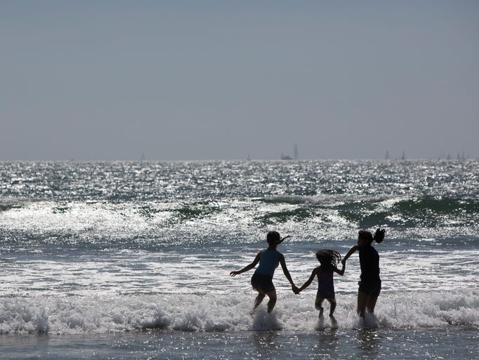 Beachgoers play in the break on Coronado Island in