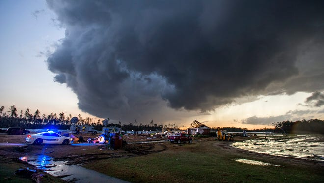 Storm clouds approach emergency crews at the scene of a house cut in half by a tornado near where seven people were killed outside Adel, Ga., on Jan. 22, 2017.