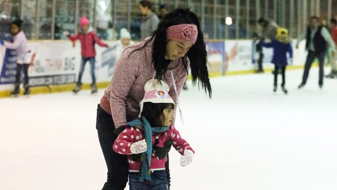 Ananet Contreras helps daughter Zoii Mendoza, 3, on the ice.