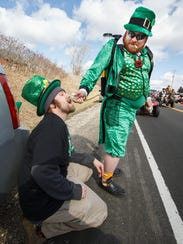 Josh Zenisek of the town of Erin gives Steve Gengler of Slinger a refreshing drink of beer during the 36th annual St. Patrick's Day Parade in 2016. Every year thousands of spectators line the streets for the parade.