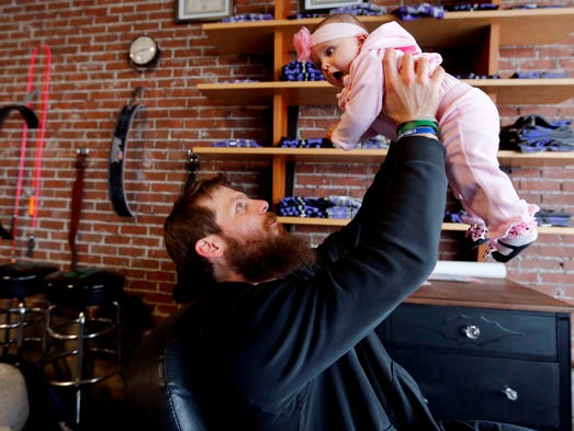 Nate Yoho lifts his five-month old daughter, Caralyn, while taking a break from work at his Crossfit studio on Merle Hay Road in Des Moines.   Caralyn was born from a surrogate mother.  Nate's wife, Laura, died of brain cancer shortly before her birth.