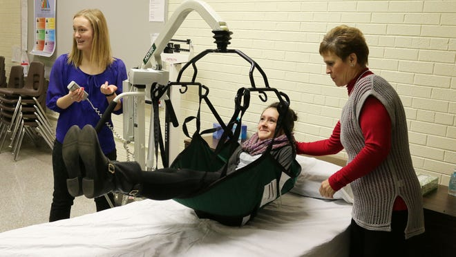 Sheboygan South student Sammy Hoyt, 18, left, demonstrates techniques for raising fellow student Mia Rabon, 17, middle, off a bed as LTC's Cindy Hogfeldt observes Tuesday at South High School.
