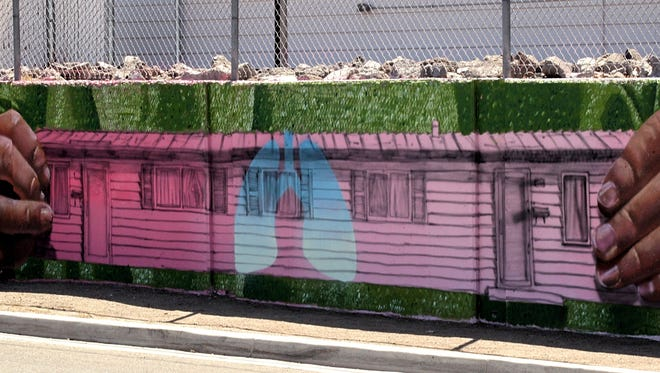 This photo shows a portion of a mural that spans along a retaining wall on East 10the Street. The mural depicts healthier lifestyles among Reno residents. It was painted by artist Erik Burke.