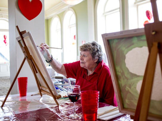 Resident Kathleen Lindbloom paints with others during