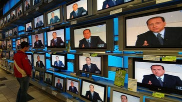 A man watches Italian premier Silvio Berlusconi on television sets in a store in Milan, Italy, in this April 3, 2006 photo.