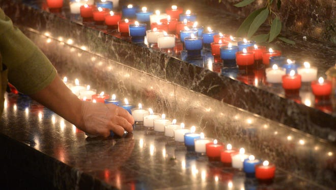 A woman places a candle onto the steps of Cathedral of St. John the Evangelist during a vigil for Mayci Breaux and Jillian Johnson Sunday evening.