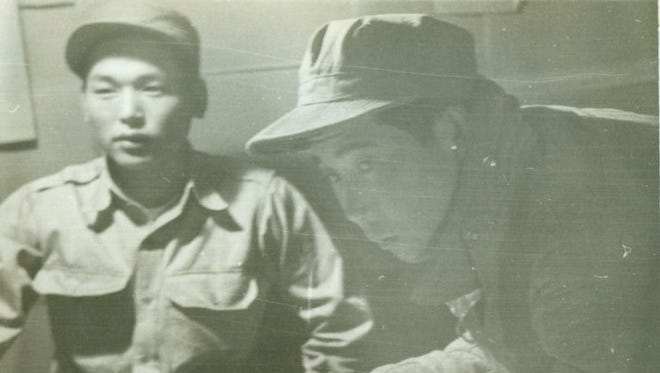 """In a faded Al Cooper photo, """"Lt. Cho"""" signs his surrender statement with ChaWal Bin seated at left."""