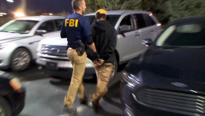 In Detroit, an FBI agent takes a suspected pimp into custody as part of Operation Cross Country. The operation targeted individuals all over the country suspected of trafficking children for sex.