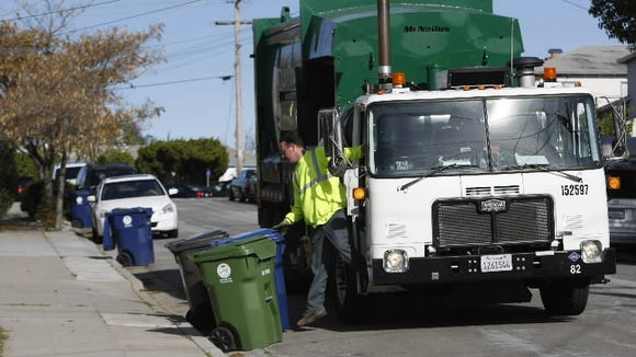 A Waste Management employee collects garbage in Castro