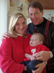 Jim Kelly and his wife, Jill, pose with their son, Hunter, in the living room of their Orchard Park home on Wednesday, Feb. 10, 1999.