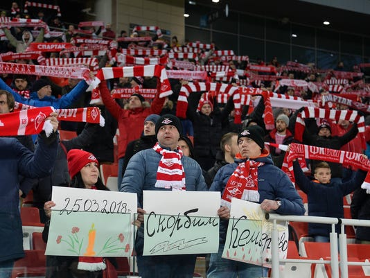 Spartak Moscow's fans hold handmade posters reading 'March 25, 2018, mourn, remember, Kemerovo' during the Russian premier league soccer match between Spartak Moscow and Tosno at the Otkrytiye Arena in Moscow, Russia, Saturday, March 31, 2018. Russian soccer teams played in near silence on Saturday as the country mourned 64 people killed in a shopping mall fire. Fan groups across the country agreed not to sing for the first halves of their league games as a mark of respect after Sunday's fire in the Siberian city of Kemerovo shook the nation. (AP Photo/Ivan Vodopianov)