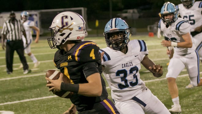 Calvary Day freshman quarterback Jake Merklinger (4) evades the grasp of North Cobb Christian's Sharnard Banks (33) during  first-half action Friday at Calvary. North Cobb Christian won 34-0.