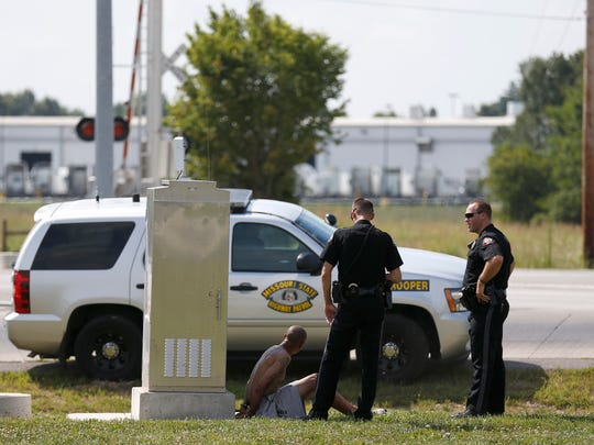 A man is detained as police and sheriffs deputies investigate