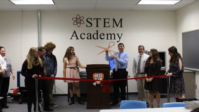 Connor Bondi, a senior at Cumberland Regional High School, presents scissors created by the laser etcher and 3-D printer to cut the red ribbon at the grand opening of the school's STEM Lab.