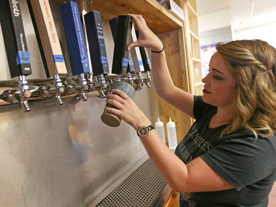General manager Molly Grooms pours an IPA, Nancy Brew and the Hoppy Boys, at the new Books & Brews location in Zionsville, Ind., during its soft opening for mug club members, Wednesday, June 29, 2016. The taproom and used bookstore is open to the public July 1, 2016.