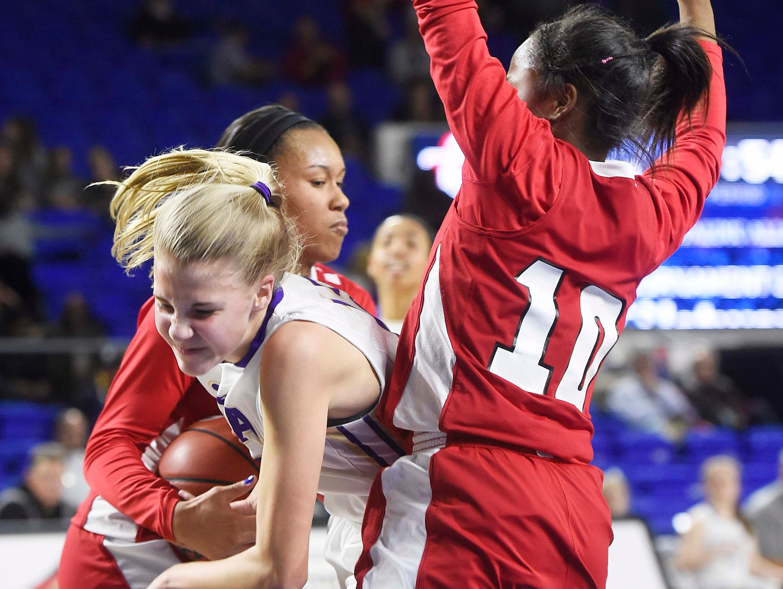 CPA's Carrington Washburn (12) collides with East's Le'Jzae Davidson, right, and Kaia Upton (14) left, as East Nashville leads 25-24 at the half n the Division I Class AA Girl's basketball tournament at the Murphy Center on MTSU's campus March 10, 2016 in Murfreesboro, Tenn.