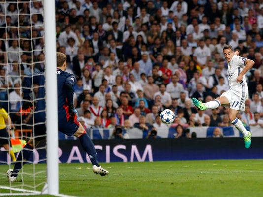 Real Madrid's Lucas Vazquez, right, challenges Bayern goalkeeper Manuel Neuer during the Champions League quarterfinal second leg soccer match between Real Madrid and Bayern Munich at Santiago Bernabeu stadium in Madrid, Spain, Tuesday April 18, 2017. (AP Photo/Daniel Ochoa de Olza)