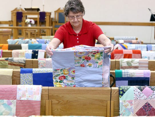 Jean Lundquist from the Peace by Piece Quilters helps
