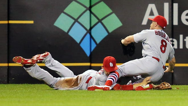 St. Louis Cardinals left fielder Stephen Piscotty (left) and center fielder Peter Bourjos (8) collide making a catch on a ball hit by Pittsburgh Pirates third baseman Josh Harrison (not pictured) during the seventh inning at PNC Park. Piscotty  was taken from the game on a stretcher.