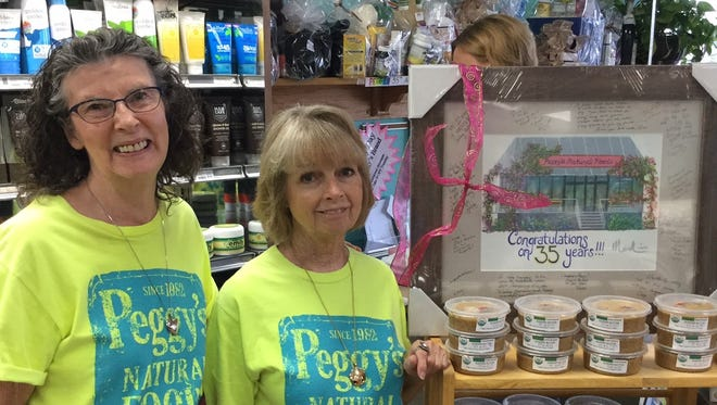 Linda Gammon and Peggy Ranger with the framed painting of the store commemorating the 35th Anniversary of Peggy's Natural Foods