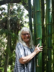 Genelle Grant stands by the Happehatchee Center's famous bamboo shoots. The stalks reach dozens of feet into the air, towering over the center's grounds.