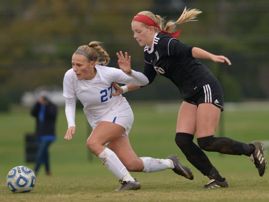 White House junior Allyson Trimmer is pushed by Greeneville senior Savannah Doty as White House goes on to win 1-0 in the Class AA state soccer championship.