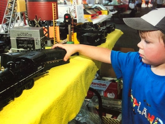 A young train enthusiast looks at a model train at