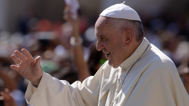 Pope Francis greets the crowd as he arrives for his weekly general audience at St. Peter's square on June 10, 2015, at the Vatican.