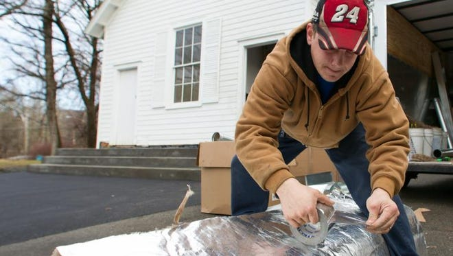 EB Design Air employee Aaron Juritsch, 28, from Suffern tapes insulation on the ductwork for the HVAC unit being installed at the Pyngyp Schoolhouse in Stony Point on Saturday, Dec. 7, 2013. Design Air is donating the labor and Lennox donated the HVAC unit.