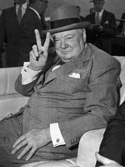 "British Prime Minister Winston Churchill responds with the ""V"" for victory sign he made a trademark during World War II as spectators cheer his arrival at National Airport in Washington, D.C., June 25, 1954."