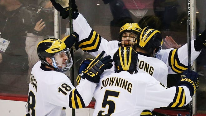 The Wolverines celebrate Tyler Motte's game-winning goal in overtime of the NCAA tournament regional semifinal against Notre Dame on Friday in Cincinnati.